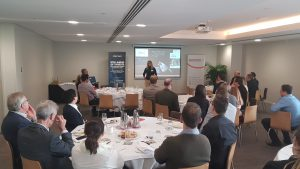 Crowd watches Alana speaking at cybersecurity event